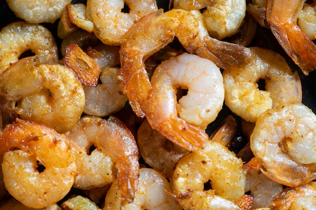 Smakelijke smakelijke sappige gepelde gebakken garnalen in een pan close-up.