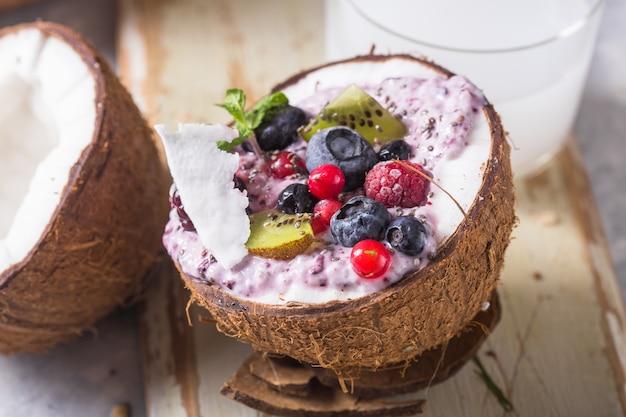 Smakelijke smakelijke smoothie acai kom gemaakt van bramen en wilde bessen. gediend in kokosnootkom. gezond leven schoon eten concept. bevroren dessert mooie room.