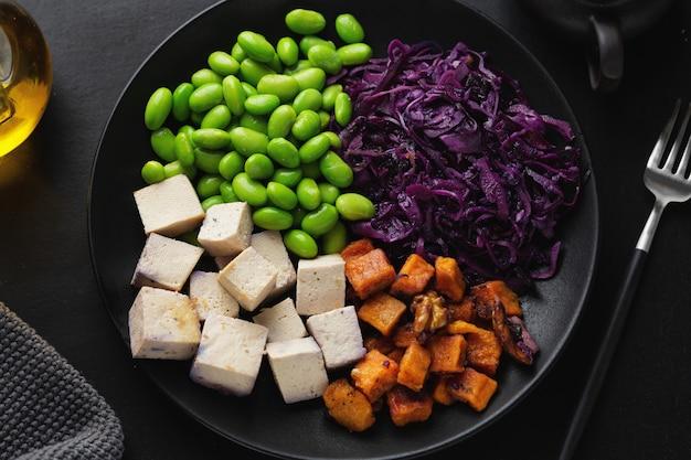 Smakelijke smakelijke veganistische kom met tofu op plaat. bovenaanzicht