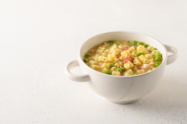 Smakelijke soep met ditalini pasta, erwten, tomaten, ham op witte tafel.