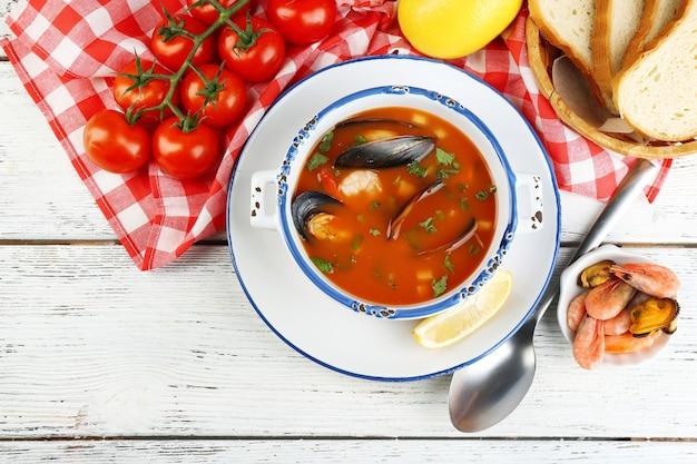 Smakelijke soep met garnalen, mosselen, tomaten en zwarte olijven in kom op houten