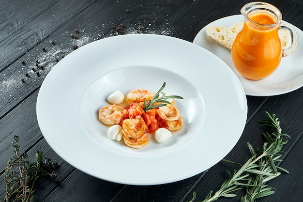 Smakelijke, spaanse tomatensoep met garnalen en mozzarella in een witte plaat op zwart hout