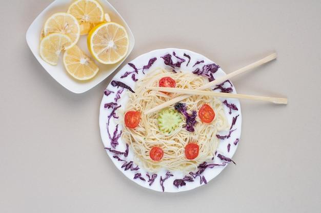Smakelijke spaghetti en plakjes citroen op een witte ondergrond