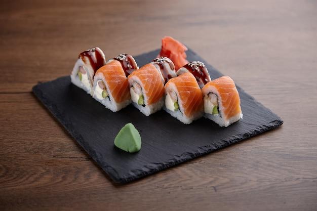 Smakelijke sushi ingesteld op een stenen plaat op een donkere houten tafel