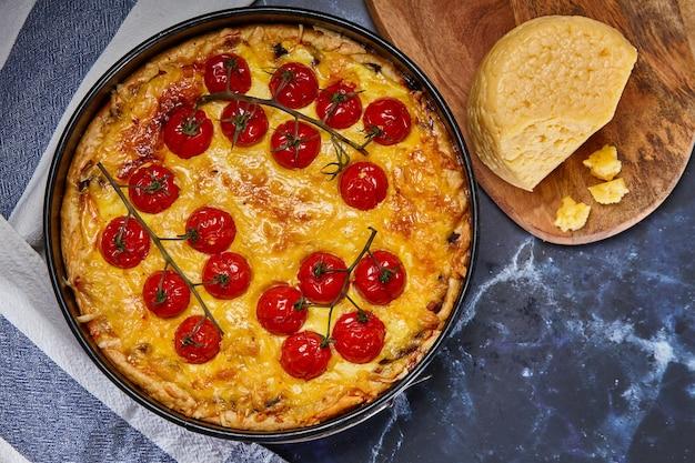 Smakelijke taart met gebakken tomaten op een tak en kip, gevuld met room, kaas en eieren.