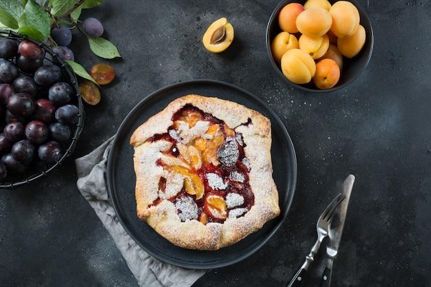 Smakelijke val pie galette met pruim en abrikoos op zwarte tafel.