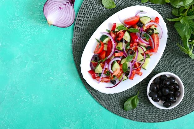 Smakelijke veganistische salade van tomaat, komkommer, rode ui en zwarte olijven