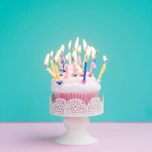 Smakelijke verjaardagsmuffin met kleurrijke kaarsen
