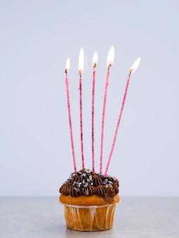 Smakelijke verjaardagsmuffin met lange kaarsen