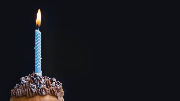 Smakelijke verjaardagsmuffin op zwarte achtergrond met exemplaarruimte