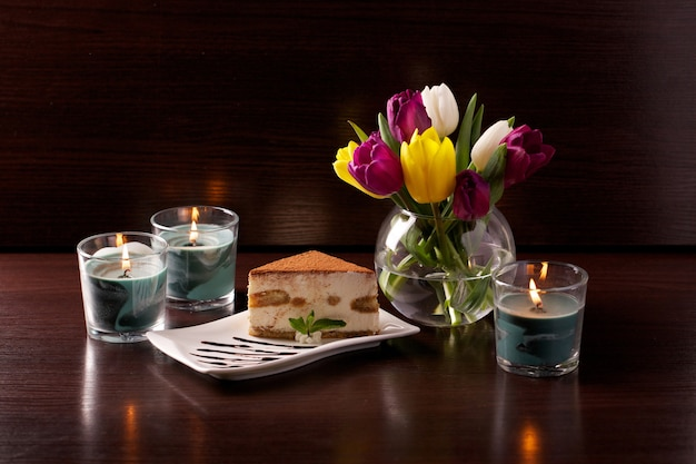 Smakelijke verse tiramisu-cake op een bruine muur met een boeket tulpen