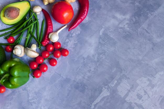 Smakelijke verse zomer rauwe biologische antioxidant kleurrijke groenten en fruit groenten: avocado, tomaat, knoflook, chili, gember geïsoleerd op een grijze achtergrond. vegan en vegetarisch gezond eten concept
