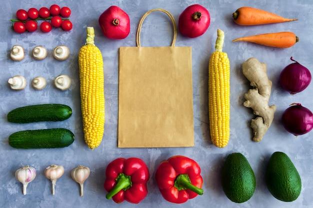 Smakelijke verse zomer rauwe biologische antioxidant kleurrijke groenten en fruit groenten: wortel, tomaat, knoflook, ui, gember, maïs geïsoleerd op achtergrond met papieren pakket. veganistisch en vegetarisch concept