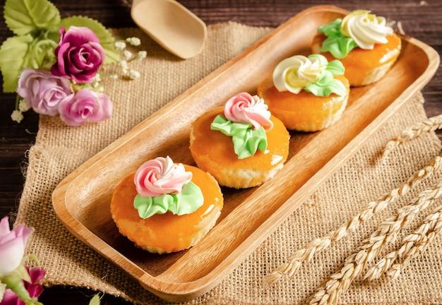 Smakelijke vintage cupcakes op houten dienblad met bloemen