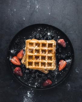 Smakelijke wafel met aardbeien en suiker, bovenaanzicht
