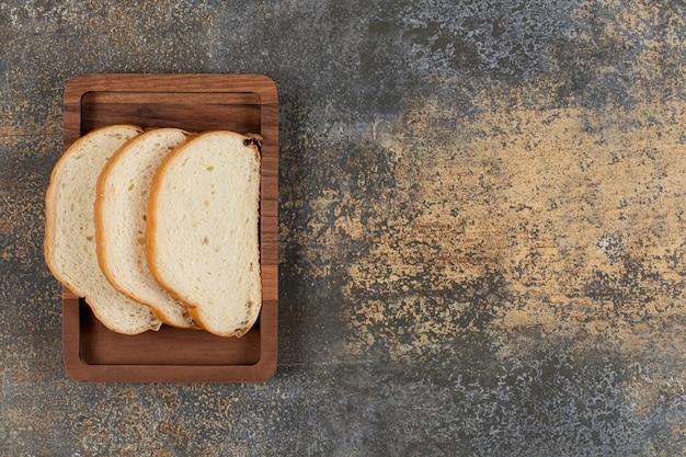 Smakelijke witte broodplakken op houten plaat.