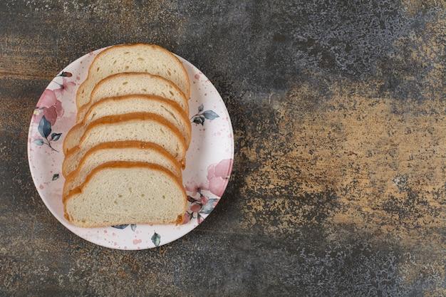 Smakelijke witte broodplakken op kleurrijke plaat.