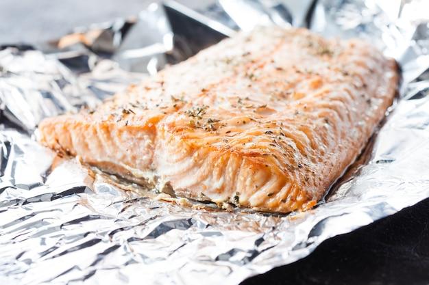 Smakelijke zalmsteak gebakken met kruiden in aluminiumfolie