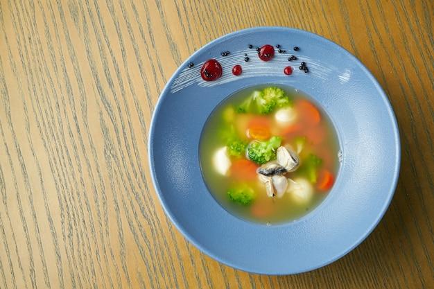 Smakelijke zeevruchtensoep. bouillon met mosselen, wortelen, broccoli en sint-jakobsschelpen in een blauw bord op een houten oppervlak