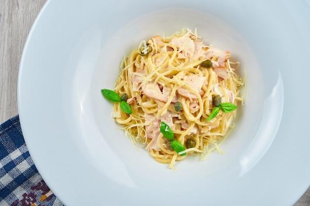 Smakelijke zelfgemaakte carbonara pasta met spek, roomsaus en basilicum in een witte plaat. close-up, bovenaanzicht. italiaanse spaghetti, foto voor het recept
