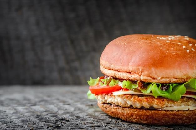 Smakelijke zelfgemaakte hamburger op donkere achtergrond