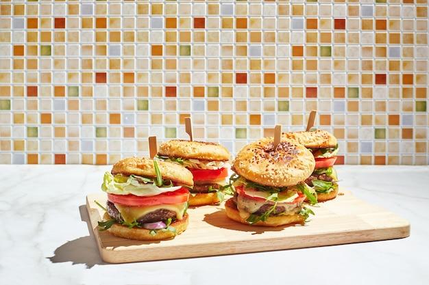 Smakelijke zelfgemaakte hamburgers op houten snijplank met fel zonlicht hamburger met kalfskoteletten pamidorom kaas rode ui sla rucola salade en frietjes fastfood concept