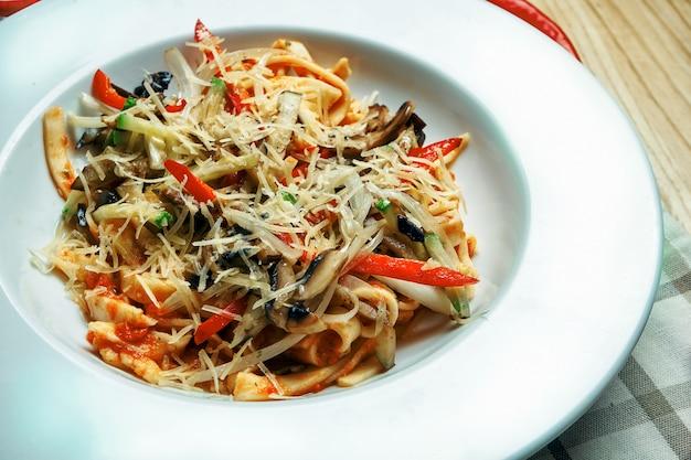 Smakelijke, zelfgemaakte pasta (tagliatelle) met rode saus, kaas en groenten in witte kom. traditioneel italiaans eten. vegetarische pasta. detailopname