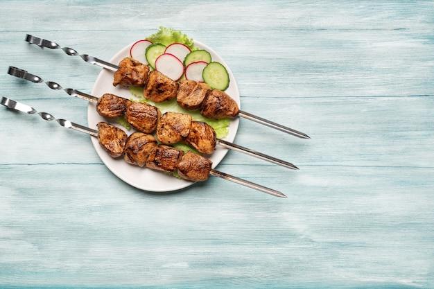 Smakelijke zelfgemaakte shish kebab, gesneden groenten bovenaanzicht op een blauwe houten achtergrond.