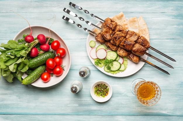 Smakelijke zelfgemaakte shish kebab groenten en glas wijn bovenaanzicht op een blauwe houten achtergrond