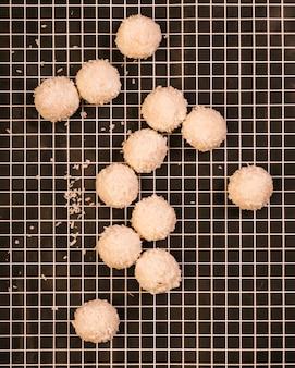Smakelijke zoete kokosnootballen op geruite textiel