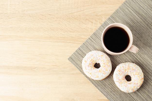 Smakelijke, zoete, verse donuts en een kop met zwarte koffie op de houten achtergrond. ontbijtconcept, fast food, koffiebar, bakkerij.