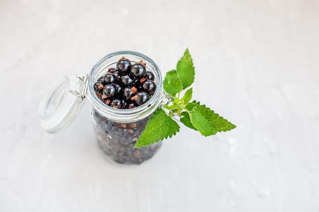 Smakelijke zwarte bes met munt in een glazen pot. witte achtergrond.