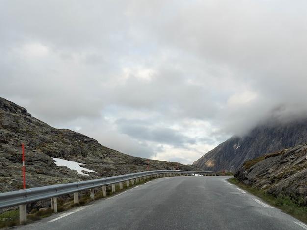 Smalle asfaltweg hoog in de bergen op een grijze bewolkte dag