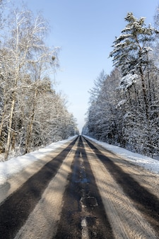 Smalle besneeuwde winterweg voor autoverkeer