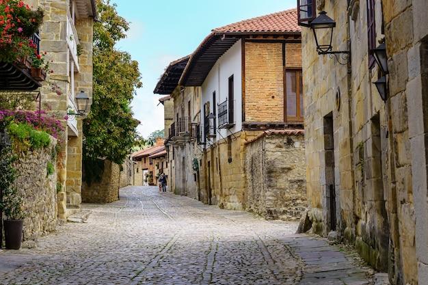 Smalle straat met oude stenen huizen en geplaveide stoep