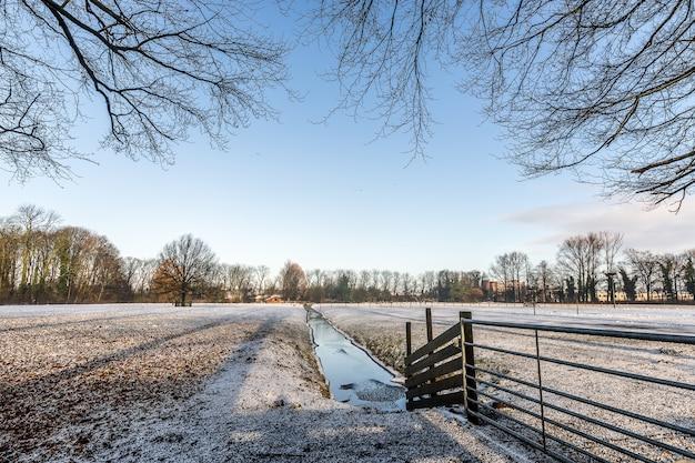 Smalle waterstroom in het midden van een leeg veld bedekt met sneeuw