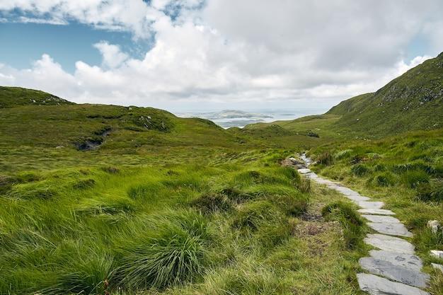 Smalle weg in connemara national park in ierland onder een bewolkte hemel