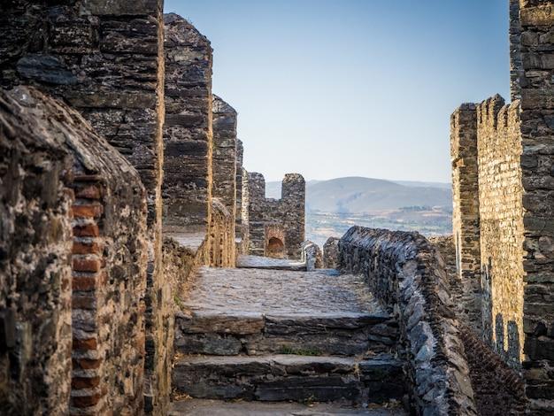 Smalle weg op de grote muren op een oud kasteel - achtergrondconcept