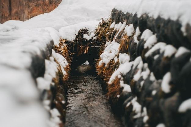 Smalle weg tussen stapels hooi bedekt met sneeuw
