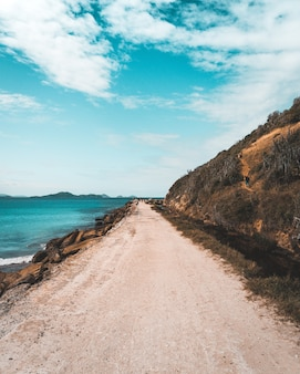 Smalle zandweg die langs de zee loopt en hoge steile heuvels met een prachtige bewolkte blauwe hemel