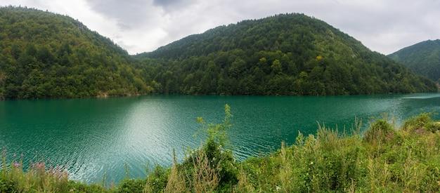 Smaragdgroen water in de rivier op een achtergrond van beboste bergen
