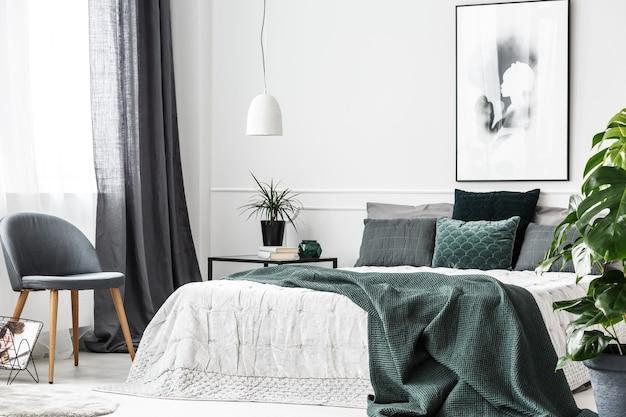 Smaragdgroene deken en kussens op wit bed in een gezellig slaapkamerinterieur met grijze stoel en poster