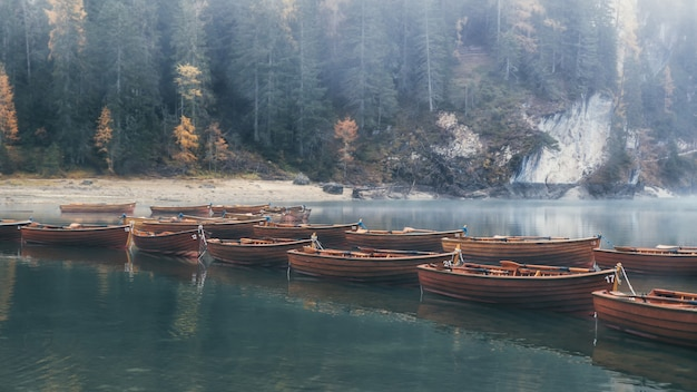 Smaragdgroene wateren van lago di braies en houten boten met nevelig bos op de achtergrond, dolomiet, italië