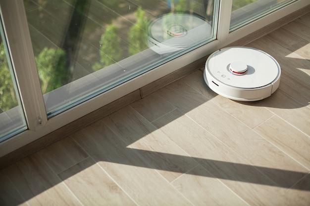 Smart house, stofzuigerrobot draait op houten vloer in een woonkamer