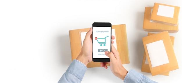 Smartphone-apparaat van de handholding en wat betreft het scherm, bedrijfseigenaar het werken. online winkelend mkb-ondernemer