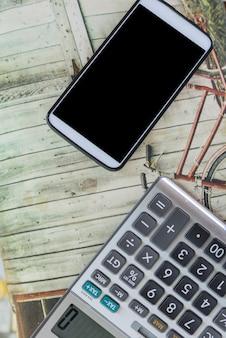 Smartphone dichtbij calculator op de lijst in bureau.