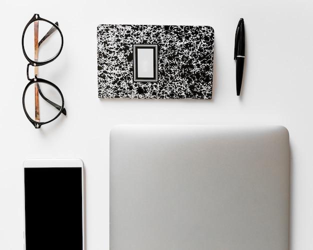 Smartphone dichtbij notitieboekje, oogglazen en pen