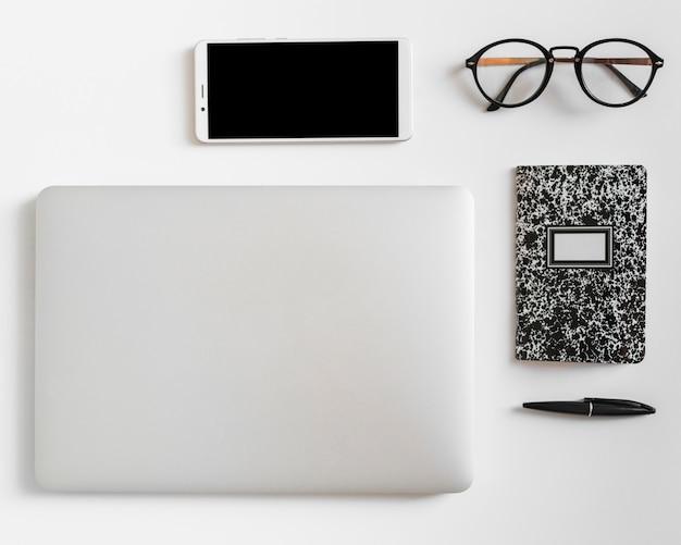 Smartphone dichtbij notitieboekje, oogglazen, tablet en pen