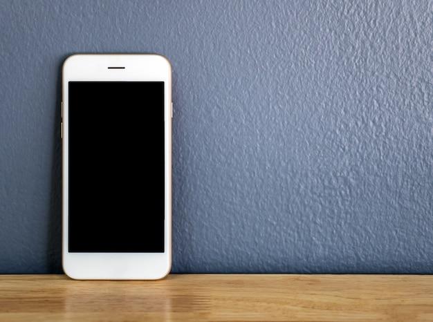 Smartphone die tegen de grijze muur leunt