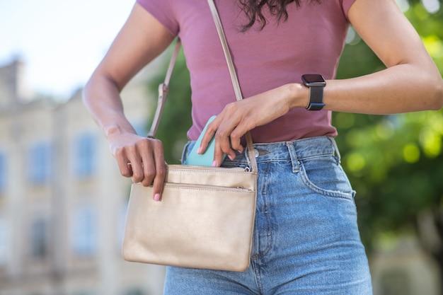 Smartphone. een meisje in spijkerbroek en roze t-shirt die smratphone in haar tas stopt